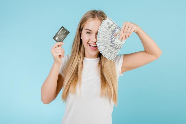 Giovane donna sorridente con i soldi della carta di credito e dei dollari in sue mani isolate sopra il blu