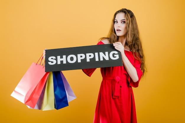 Giovane donna sorridente con il segno di acquisto e sacchetti della spesa variopinti isolati sopra giallo