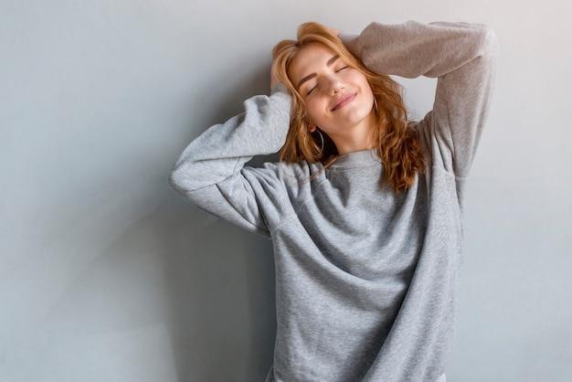 Giovane donna sorridente con le mani sulla sua testa che si leva in piedi contro la priorità bassa grigia
