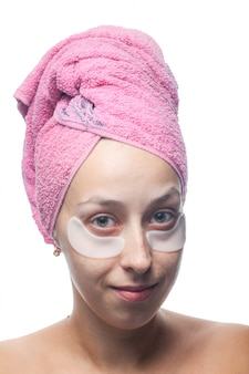 Giovane donna sorridente con le toppe bianche sotto gli occhi e un asciugamano rosa sulla sua testa isolata su bianco. ritratto del primo piano cura della pelle