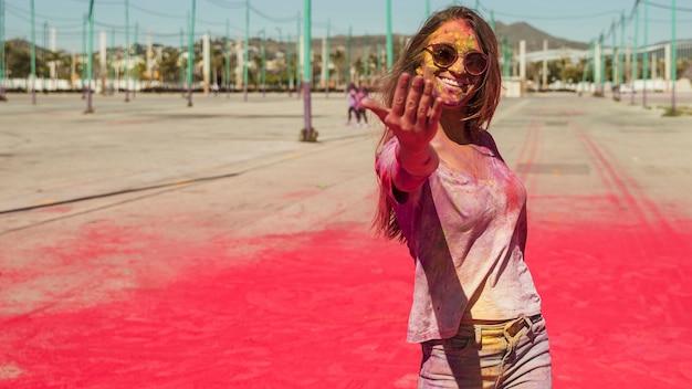 Giovane donna sorridente coperta con il colore di holi che chiama davanti alla macchina fotografica