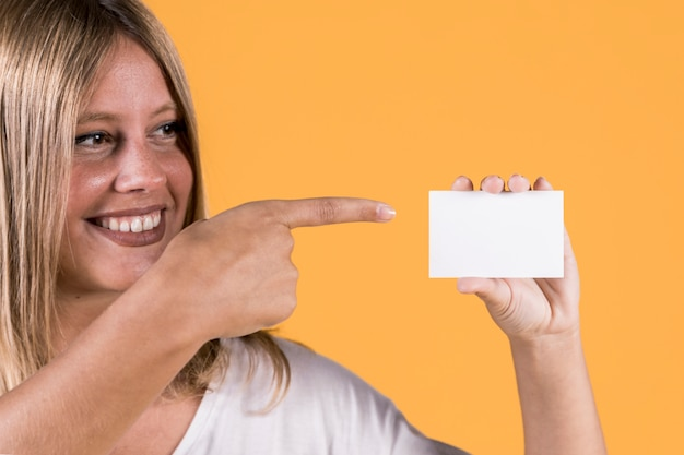Giovane donna sorridente di disabilitazione che indica sopra il biglietto da visita in bianco