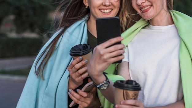 Giovane donna sorridente di vista frontale che prende un'immagine