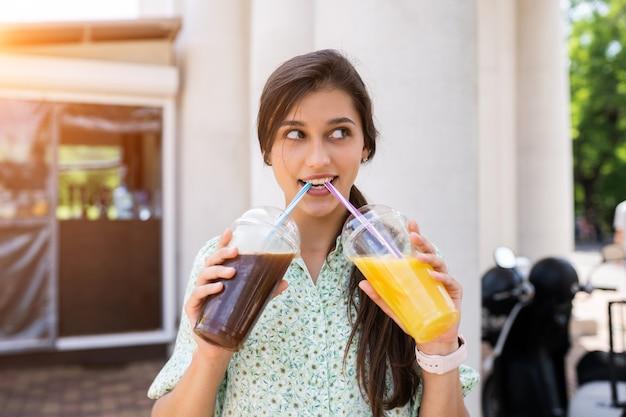 Giovane donna sorridente e beve due cocktail con ghiaccio in bicchieri di plastica con paglia sulla strada cittadina.