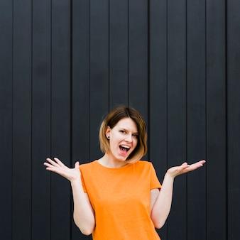 Giovane donna sorridente emozionante che scrolla le spalle contro il contesto nero