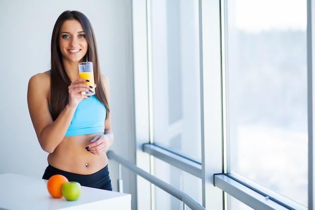 Giovane donna sorridente felice che beve il succo di arancia