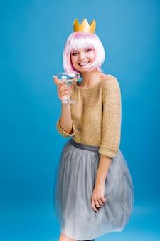 Giovane donna sorridente felice con champagne in corona d'oro che celebra la festa. maglione dorato, gonna in tulle grigio, trucco con orpelli rosa, espressione di positività.