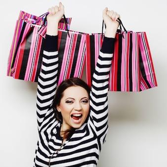 Giovane donna sorridente felice con i sacchetti della spesa.