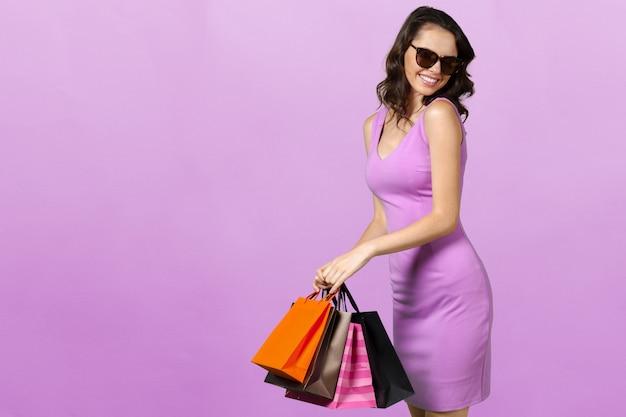 Giovane donna sorridente felice con i sacchetti della spesa