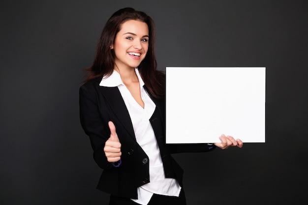 Giovane donna sorridente felice di affari che mostra insegna in bianco