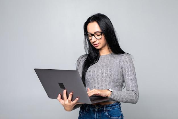 Giovane donna sorridente felice in abbigliamento casual che giudica computer portatile isolato sulla parete grigia