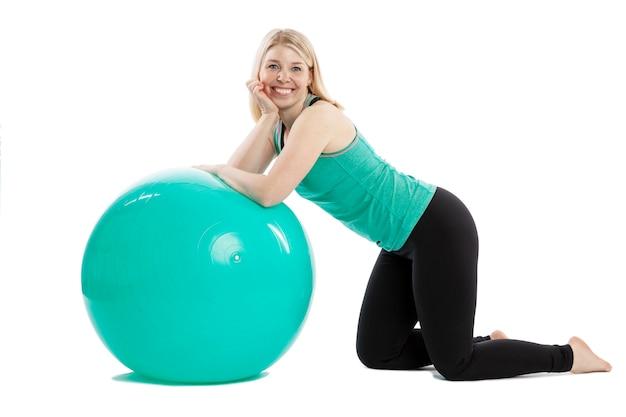 Giovane donna sorridente in abiti sportivi che fa gli esercizi con la palla di forma fisica. isolato su sfondo bianco.