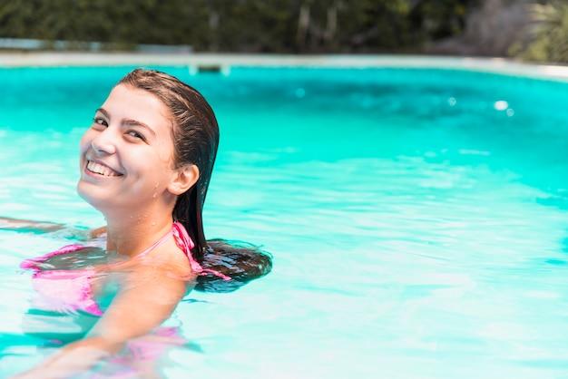 Giovane donna sorridente in bikini in piscina