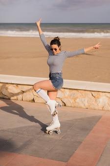 Giovane donna sorridente in pattino da rullo che mostra il segno di pace alla spiaggia