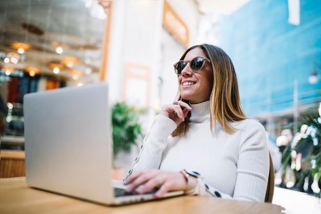 Giovane donna sorridente pensierosa che utilizza computer portatile alla tavola in caffè della via
