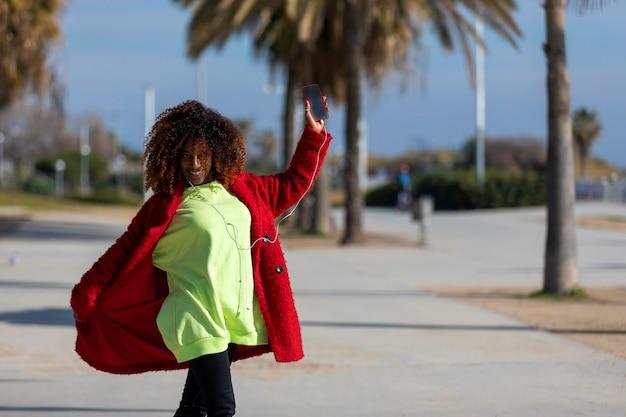 Giovane donna sorridente riccia fro in piedi all'aperto mentre sorridente e ascolto musica da auricolari in una giornata di sole