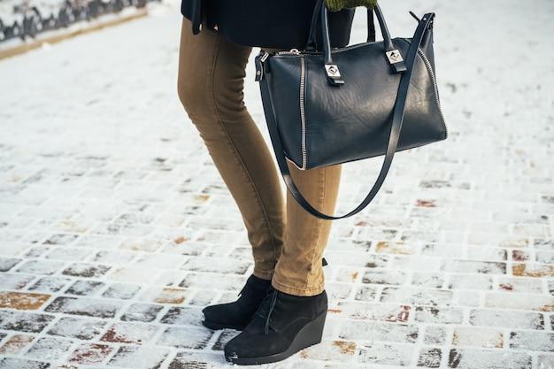 Giovane donna sottile che cammina nel parco con la borsa in inverno