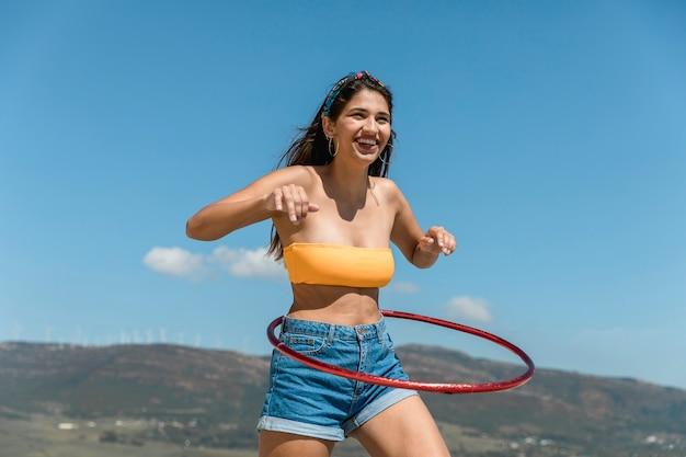 Giovane donna sottile che gira hula hoop intorno alla vita