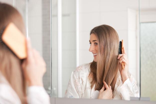 Giovane donna spazzolarsi i capelli