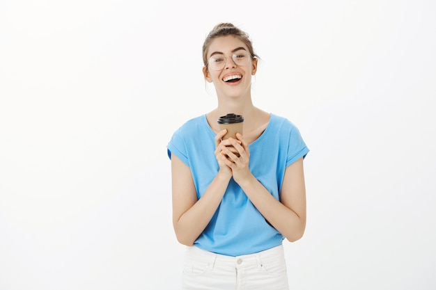 Giovane donna spensierata con gli occhiali, bere caffè e sorridere