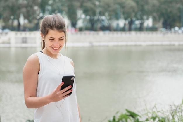 Giovane donna splendida che controlla il suo telefono