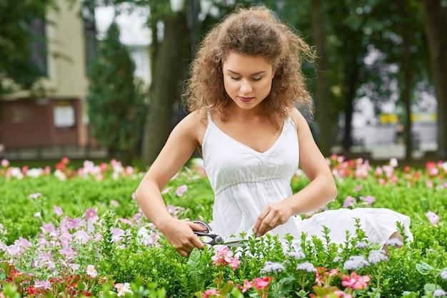 Giovane donna splendida che gode del giardinaggio delle piante della guarnizione con il concetto di godimento della natura di stile di vita di hobby di vitalità di felicità del copyspace di forbici.