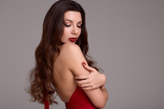 Giovane donna splendida del brunette con capelli ricci in vestito rosso