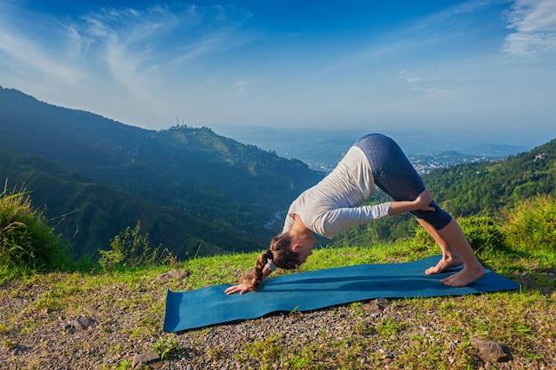 Giovane donna sportiva adatta che fa i oudoors di yoga in montagne