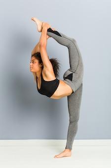 Giovane donna sportiva afroamericana che fa le pose di ginnastica ritmica