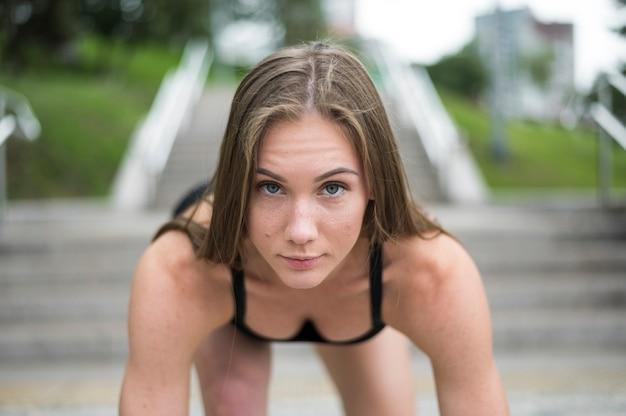 Giovane donna sportiva alla posizione di partenza pronta per iniziare
