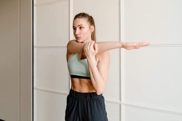 Giovane donna sportiva che allunga e che fa esercizio a casa