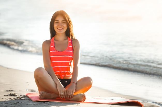 Giovane donna sportiva che fa esercizi di yoga sulla spiaggia