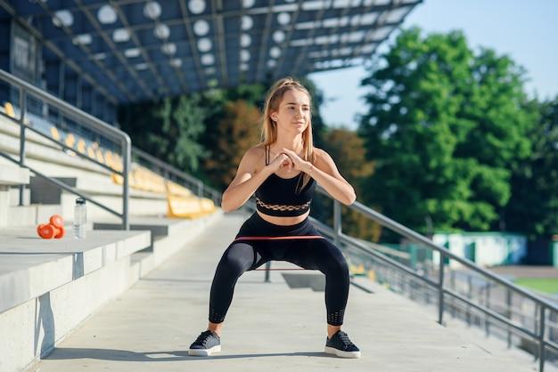 Giovane donna sportiva che fa gli esercizi con l'elastico all'aperto