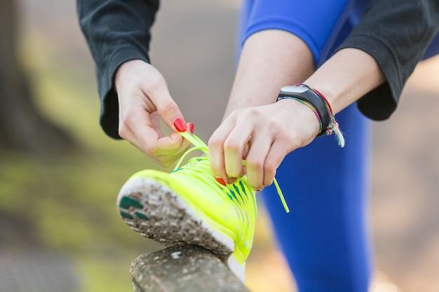 Giovane donna sportiva che fa i suoi pattini prima di correre.