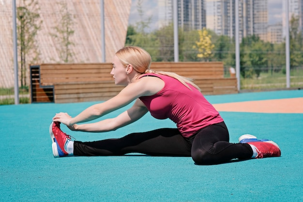 Giovane donna sportiva che fa sport all'aperto, esercizi di fitness.