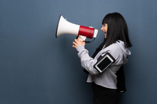 Giovane donna sportiva che grida tramite un megafono