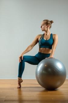 Giovane donna sportiva che si siede sul fitball, motivazione di forma fisica, fondo grigio. banner sportivo, copia spazio, bel corpo.