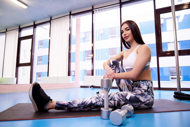 Giovane donna sportiva che si siede sul tappeto in palestra con manubri.
