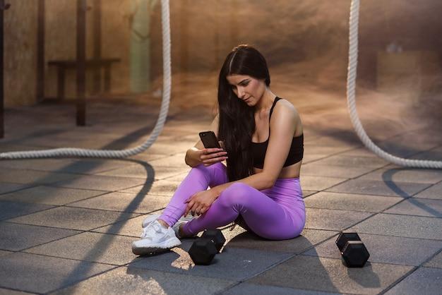 Giovane donna sportiva che utilizza smartphone durante il riposo dopo un duro allenamento in palestra.