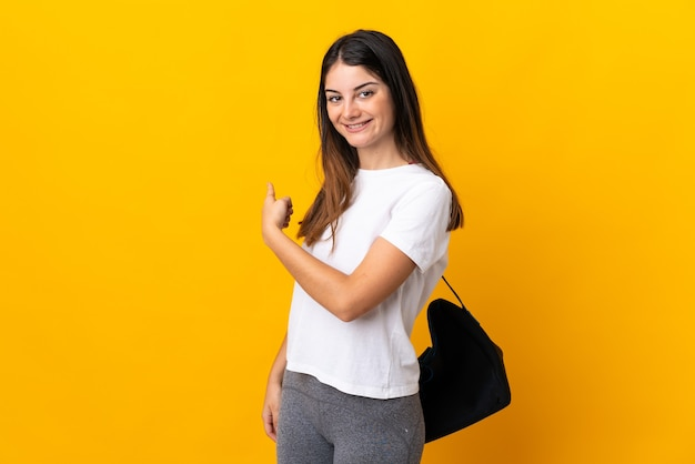 Giovane donna sportiva con borsa sportiva isolata su giallo che punta indietro