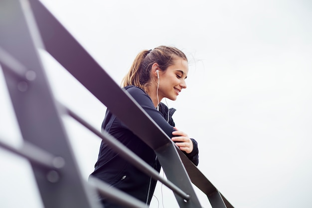 Giovane donna sportiva con le cuffie che si appoggia recinto e che distoglie lo sguardo all'aperto