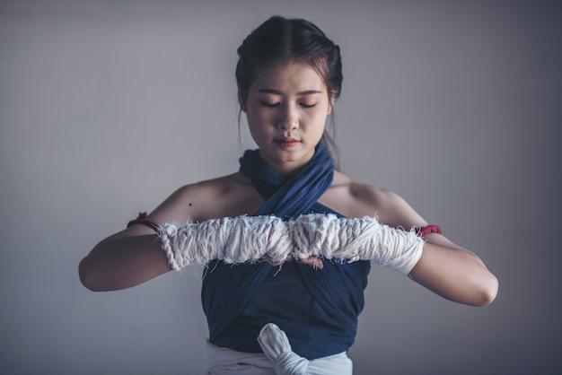 Giovane donna sportiva del pugile con bende bianche.