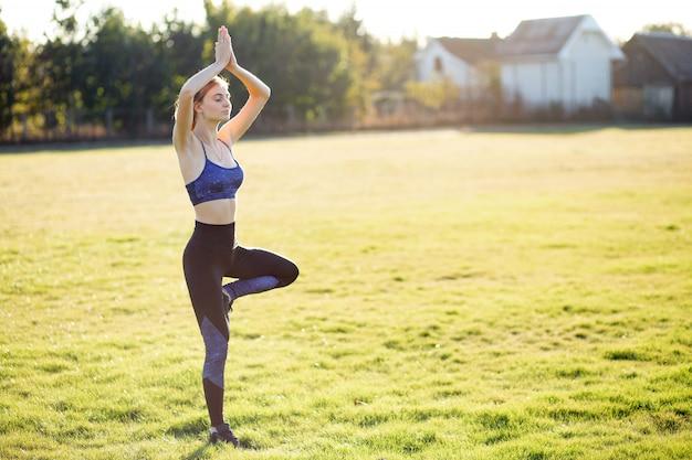 Giovane donna sportiva facendo esercizi di yoga fitness in una calda giornata estiva all'aperto.