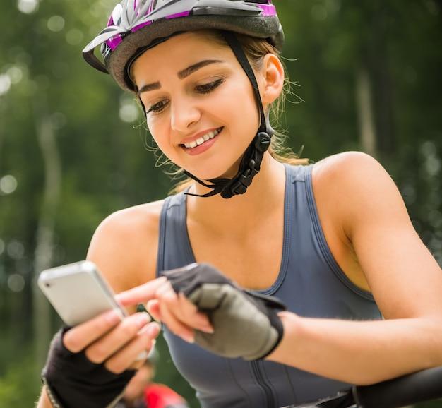 Giovane donna sportiva in casco con la bicicletta che ha resto.