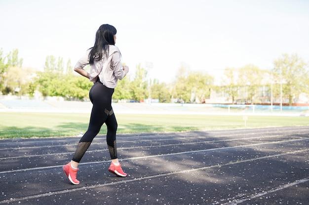 Giovane donna sportiva in esecuzione al mattino. ragazza fitness