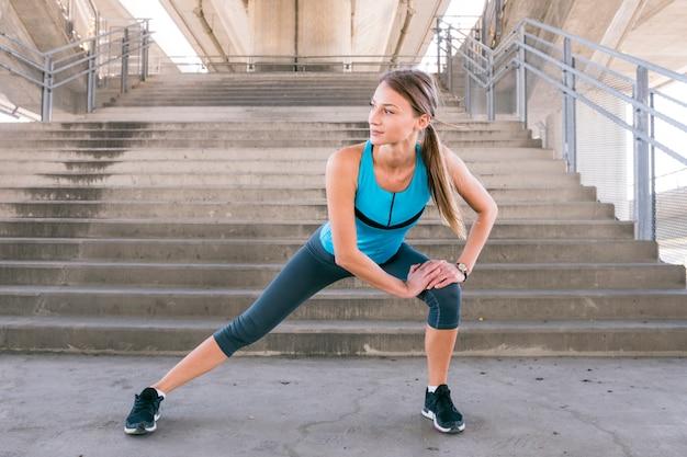 Giovane donna sportiva in piedi giù per la scala che si estende le gambe