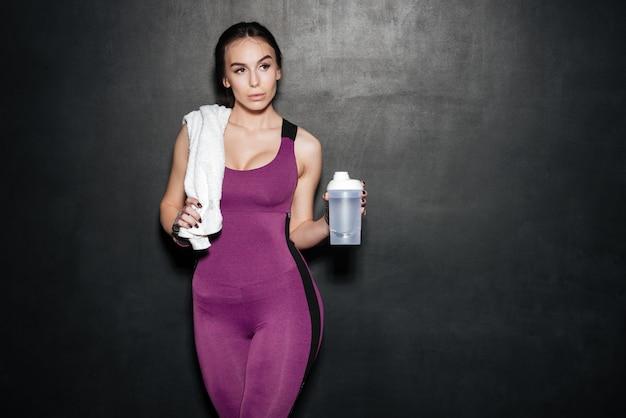 Giovane donna sportiva in tuta sportiva con asciugamano e bottiglia d'acqua