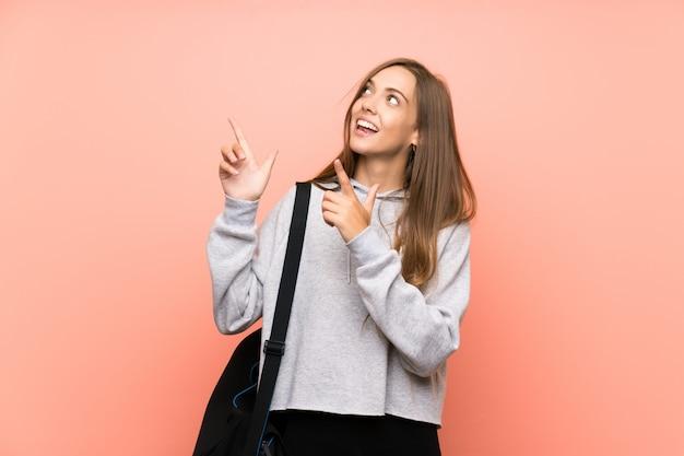 Giovane donna sportiva rosa che punta con il dito indice un'ottima idea