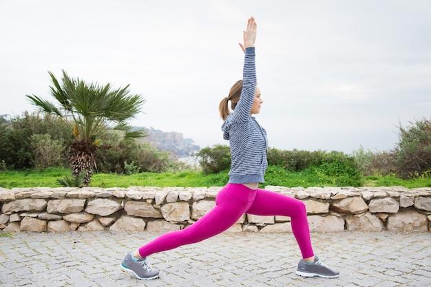 Giovane donna sportiva seria che si esercita all'aperto