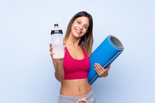 Giovane donna sportiva sopra isolato blu con bottiglia d'acqua sport e con una stuoia